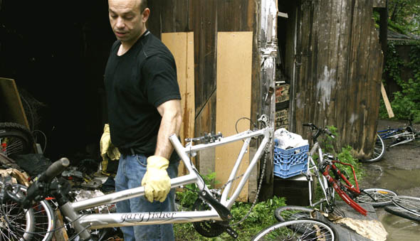 Det. Izzy Bernardo with the Major Crimes Unit, 14 division takes a bike from a Parkdale garage from a stash of recovered stolen bikes