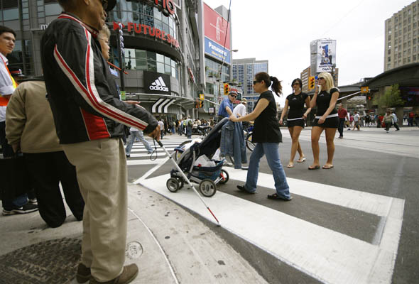 Davis McCarroll, 91, gets ready to cross the new scramble pedestrian crossing at Yonge and Dundas in Toronto