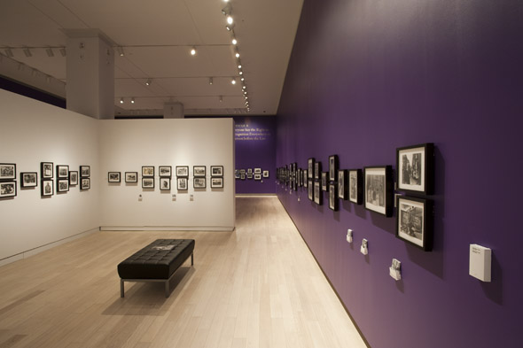 Inside gallery with long purple wall and framed black and white prints