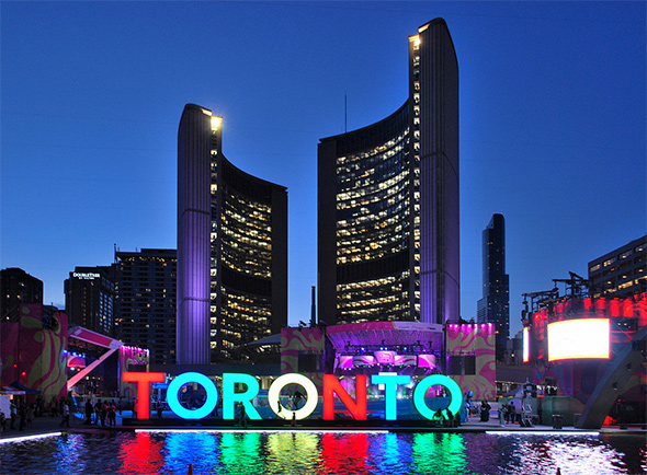 The large, multi-coloured sign saying TORONTO in capitals, lit up at night over the water at Nathan Phillips Square.