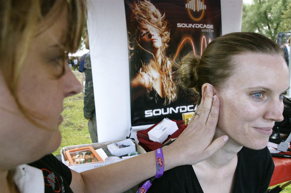 A woman gets fitted for Soundcage earplugs by Sonomax during the Virgin Music Festival in Toronto