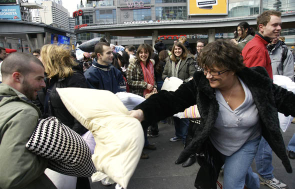 Adults having fun at the pillow fight at Yonge-Dundas Square in Toronto 2009