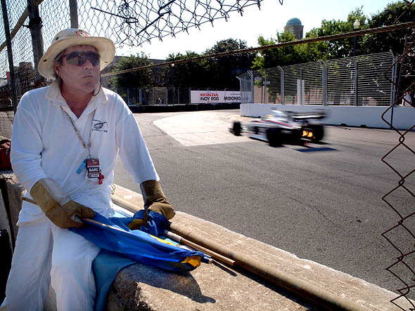 A flagman waits at a corner during Indy practices